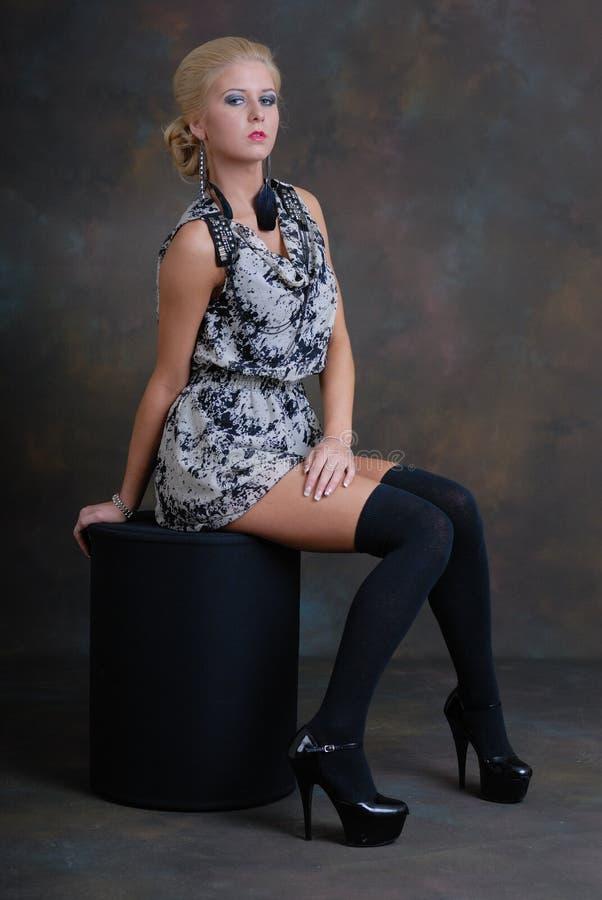 Beau jeune femme dans la robe et les bas images stock