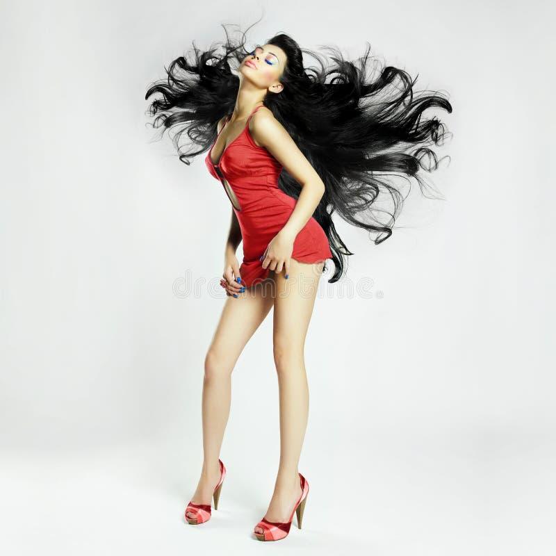 Beau jeune femme dans la robe rouge images stock