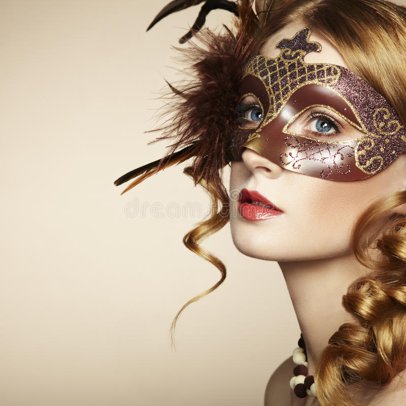 Beau jeune femme dans le masque vénitien brun photographie stock