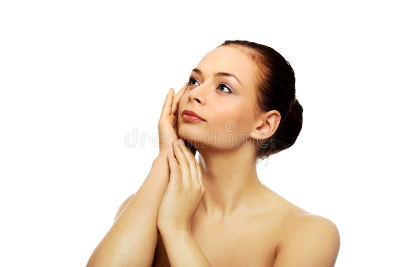 Beau jeune femme touchant son visage image stock