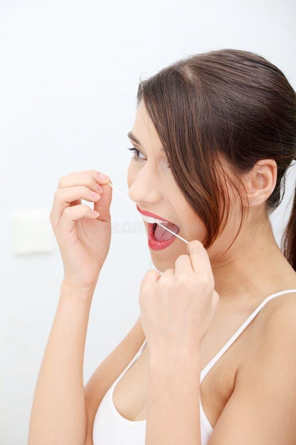 Beau jeune femme utilisant la soie dentaire photo stock
