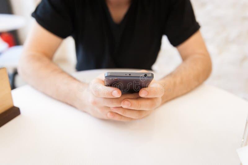 Beau, jeune homme à l'aide de son téléphone portable dans un secteur public, à la table images libres de droits