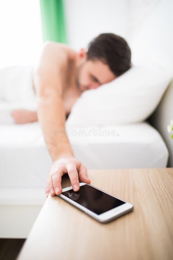 Beau jeune homme se réveillant avec le réveil mobile pendant le matin dans le lit photo stock