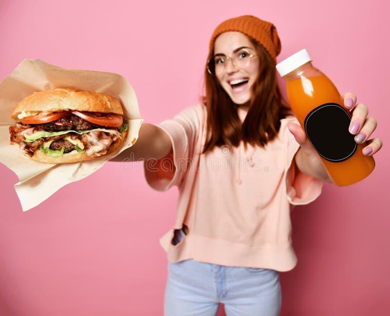 Beau jeune modèle blond de sourire de femme en hamburger de participation de tissu de hoodie de hippie et jus de bouteille image libre de droits