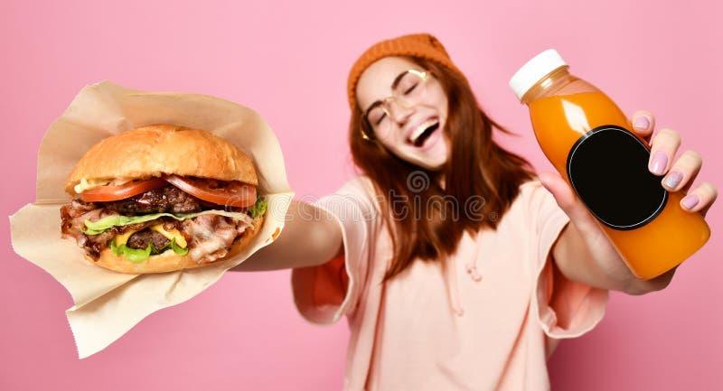 Beau jeune modèle blond de sourire de femme en hamburger de participation de tissu de hoodie de hippie et jus de bouteille photo stock
