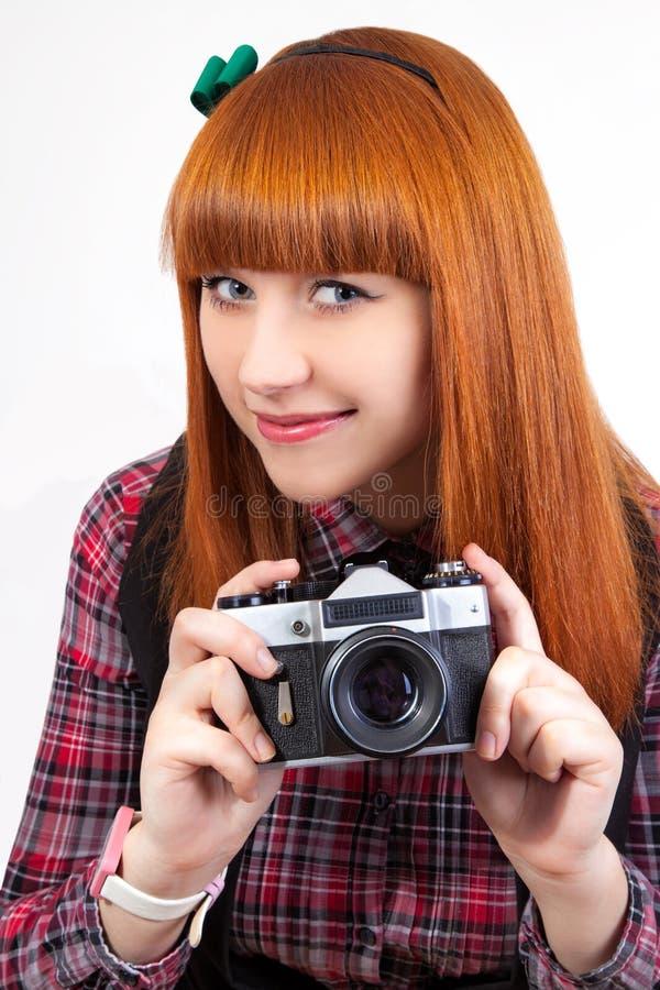Beau jeune rouge - femelle de cheveu avec le vieil appareil-photo photographie stock libre de droits