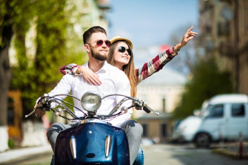 Beau jeune scooter d'équitation de couples ensemble tandis que femme heureuse se dirigeant loin et souriant image stock