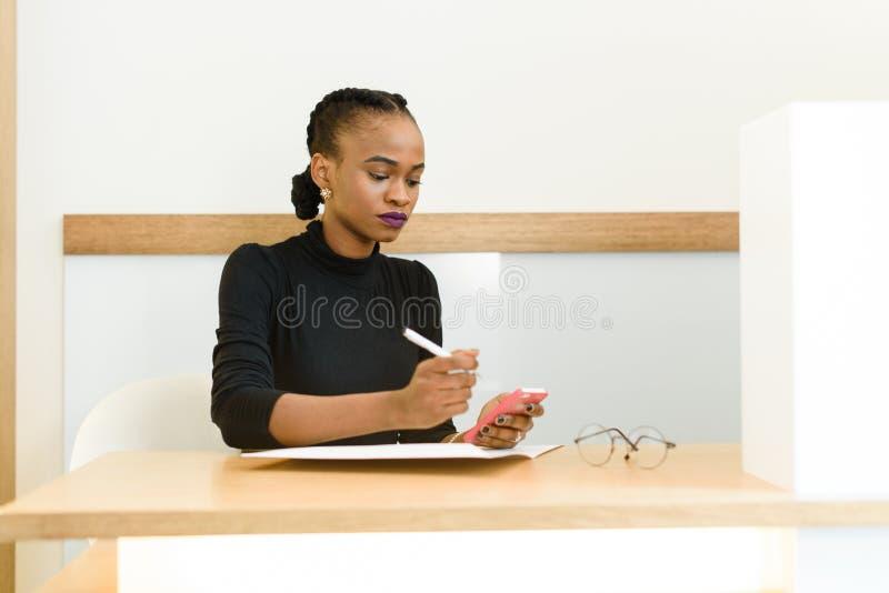 Beau jeune service de mini-messages américain africain ou noir de femme au téléphone mobile de téléphone portable dans le bureau photo libre de droits