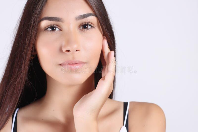 Beau jeune traitement crème cosmétique de application modèle sur son visage images stock