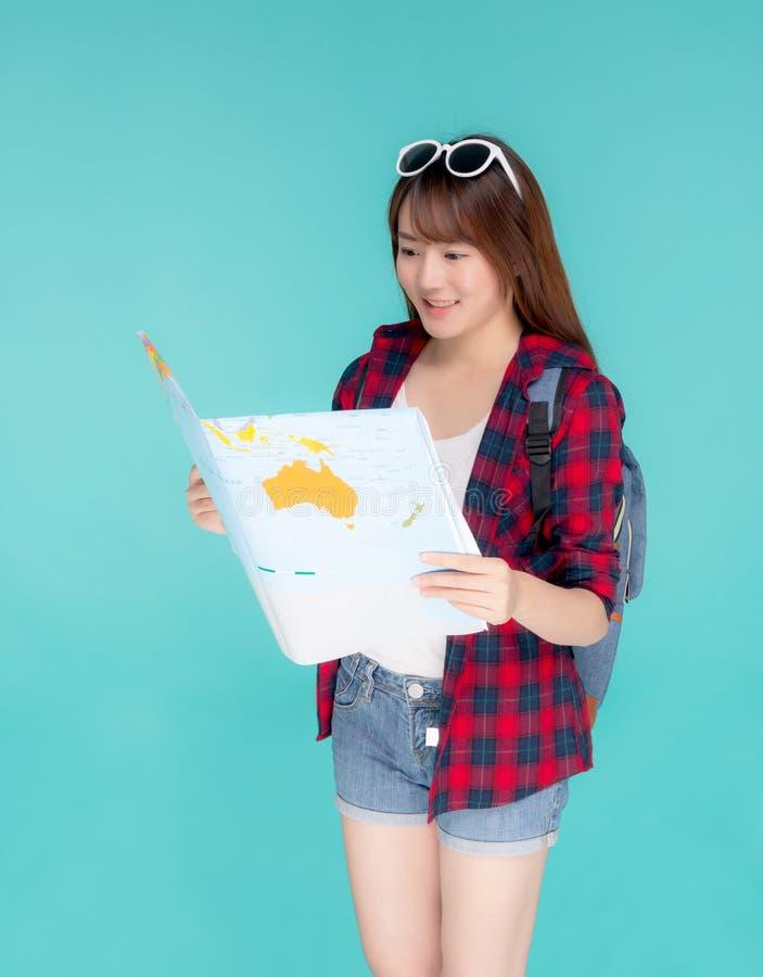 Beau jeune voyage asiatique heureux de femme tenant et regardant une carte de papier d'isolement sur le fond bleu photo stock
