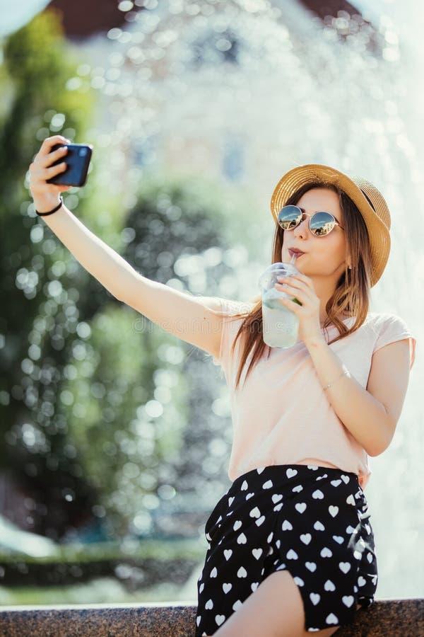 Beau joli mojito de boissons de jeune femme faisant le selfie dans la rue de ville d'été photo libre de droits
