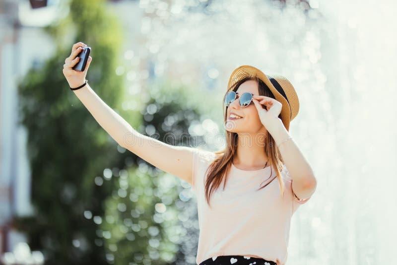 Beau joli mojito de boissons de jeune femme faisant le selfie dans la rue de ville d'été image stock