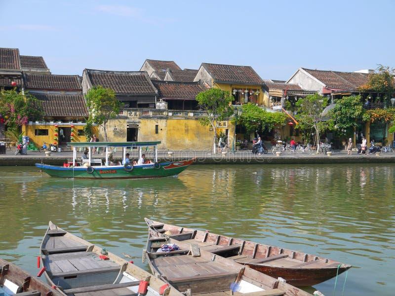 Beau jour en ville antique de Hoi An avec la vue des bateaux traditionnels, des maisons jaunes et des touristes photographie stock libre de droits