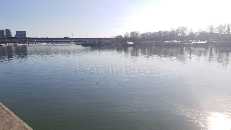 Beau lac artificiel avec des réflexions du soleil, des arbres et du barrage photo stock