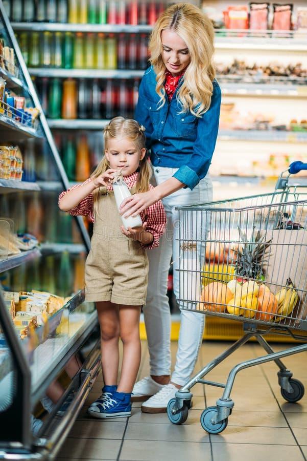 beau lait de achat de mère et de fille photo stock