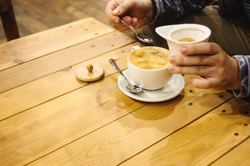 Beau latte étonnant élégant sur des mains du ` s d'un bureau en bois et d'homme images stock