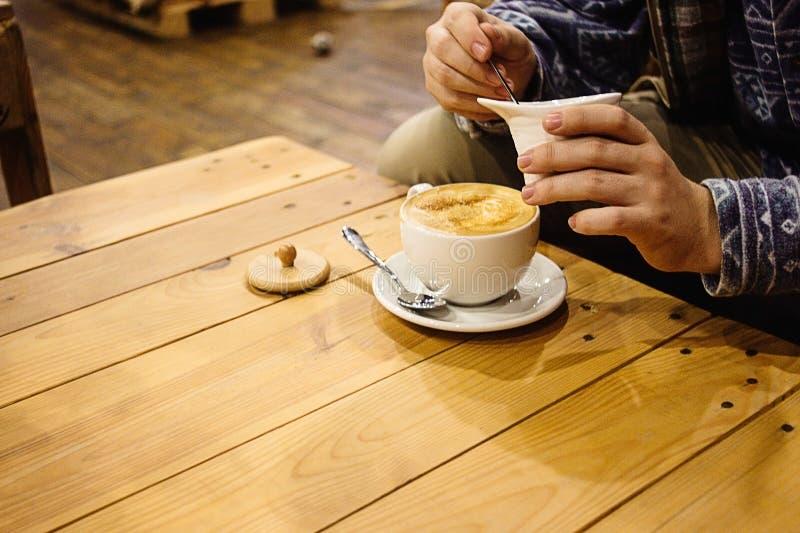 Beau latte étonnant élégant sur des mains du ` s d'un bureau en bois et d'homme photographie stock