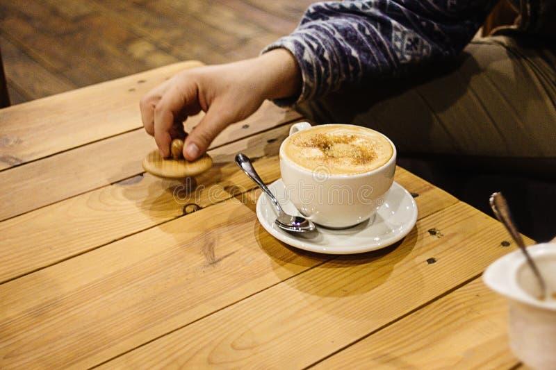 Beau latte étonnant élégant sur des mains du ` s d'un bureau en bois et d'homme photo stock