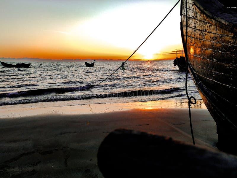 Beau lever de soleil au-dessus d'un vieux bateau de pêche en bois sur un Pebble Beach image stock