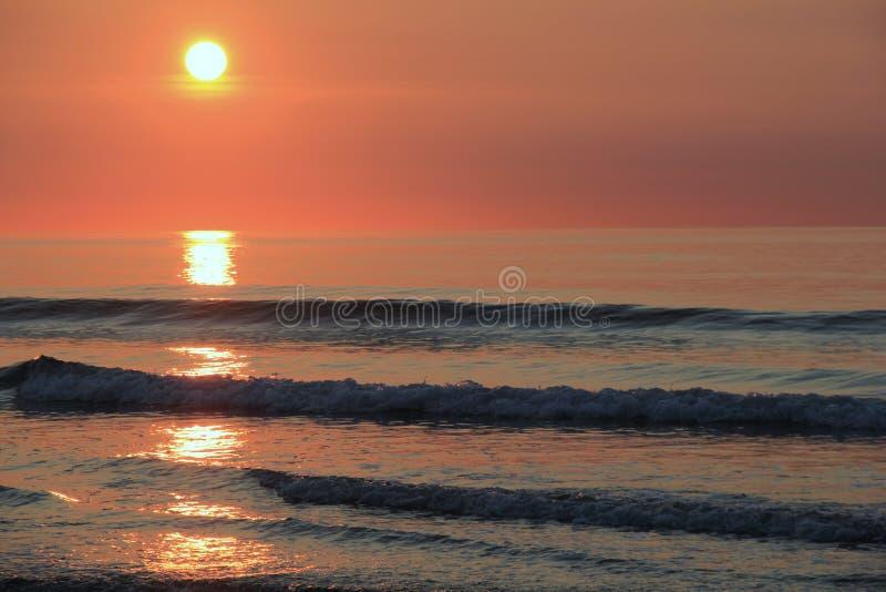Beau lever de soleil avec les teintes oranges au-dessus de l'eau image libre de droits