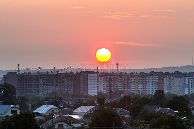 Beau lever de soleil dans des banlieues de ville Le grand soleil blanc et jaune lumineux au-dessus du hauts immeuble, grues à tou image stock