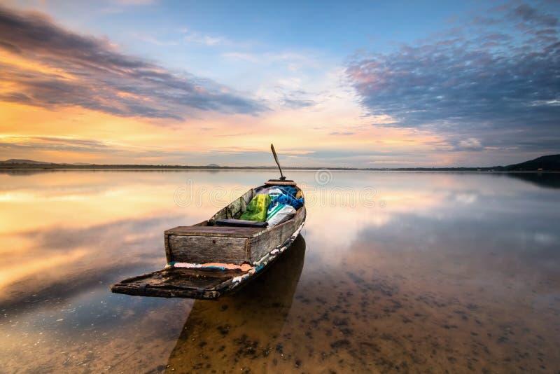 Beau lever de soleil majestueux par le bord de lac avec le bateau de pêche photos stock