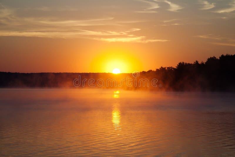 Beau lever de soleil sur le lac Horizontal de début de la matinée brume sur l'eau, des silhouettes de forêt et les rayons de l'au photos stock