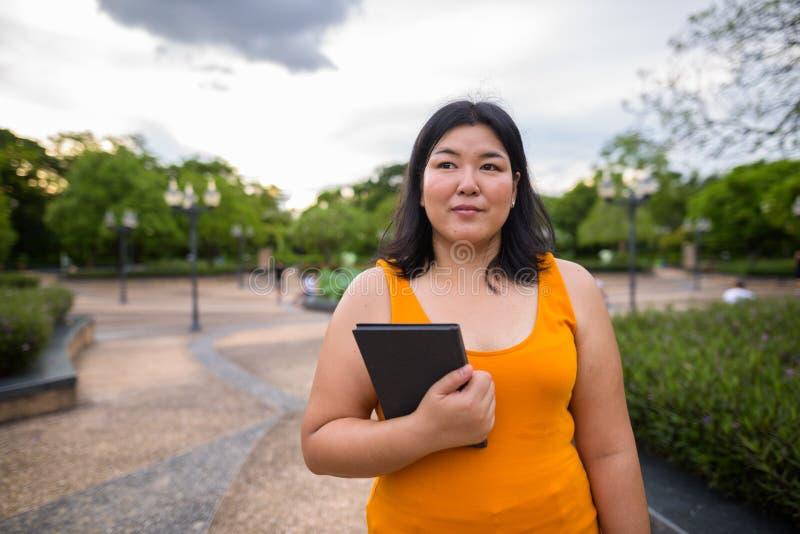 Beau livre asiatique de poids excessif de participation de femme en parc image libre de droits