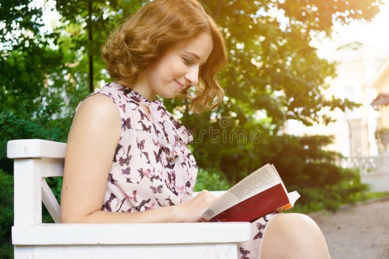 Beau livre de lecture de jeune femme sur le banc de parc photo stock