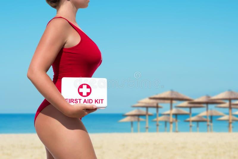 Beau maître nageur de femme dans un maillot de bain rouge avec un kit de premiers secours sur le fond de parapluies de mer et de  photo libre de droits