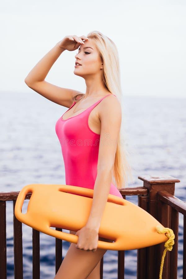 Beau maître nageur sexy de femme avec le conseil de délivrance observant sur la plage au safity sur l'eau Le travail de maître na image stock