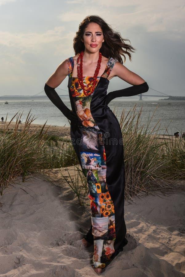 Beau mannequin avec du charme dans la robe de soirée élégante noire et gants posant sur la plage images stock