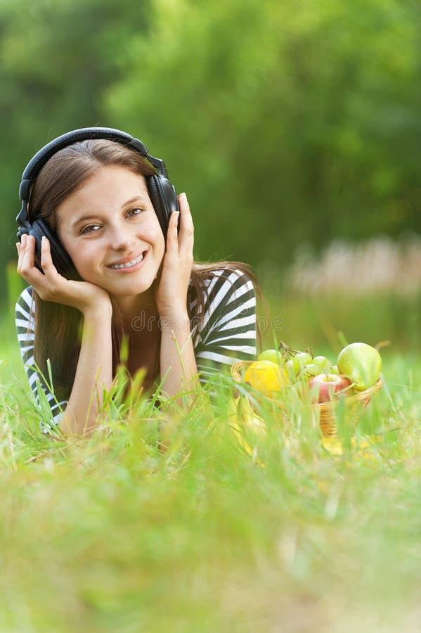 Femme écoutant la musique à travers images stock