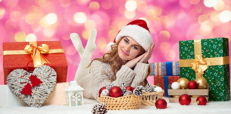 Beau mensonge de jeune fille dans le chapeau de Santa avec des boîte-cadeau - concept de vacances images stock