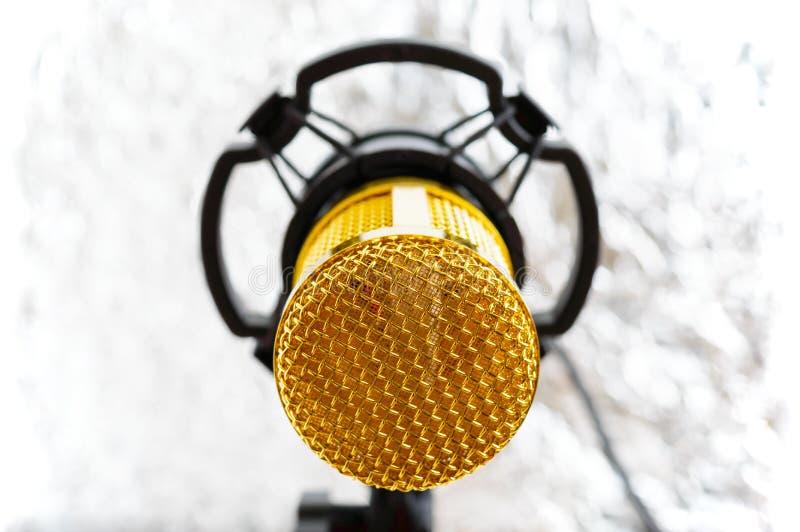Beau microphone d'or sur un fond brouillé clair photo libre de droits