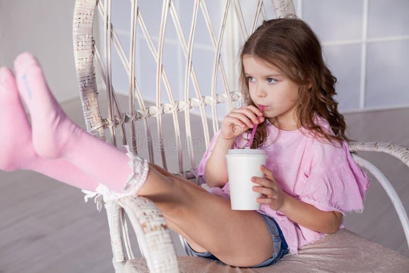 Beau milkshake potable de petite fille par une paille photographie stock libre de droits