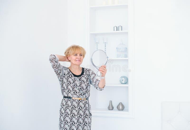 Beau miroir de main supérieur de participation de femme au studio blanc photos libres de droits