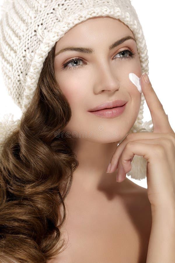 Beau modèle appliquant une crème sur la protection de visage contre l'hiver image libre de droits