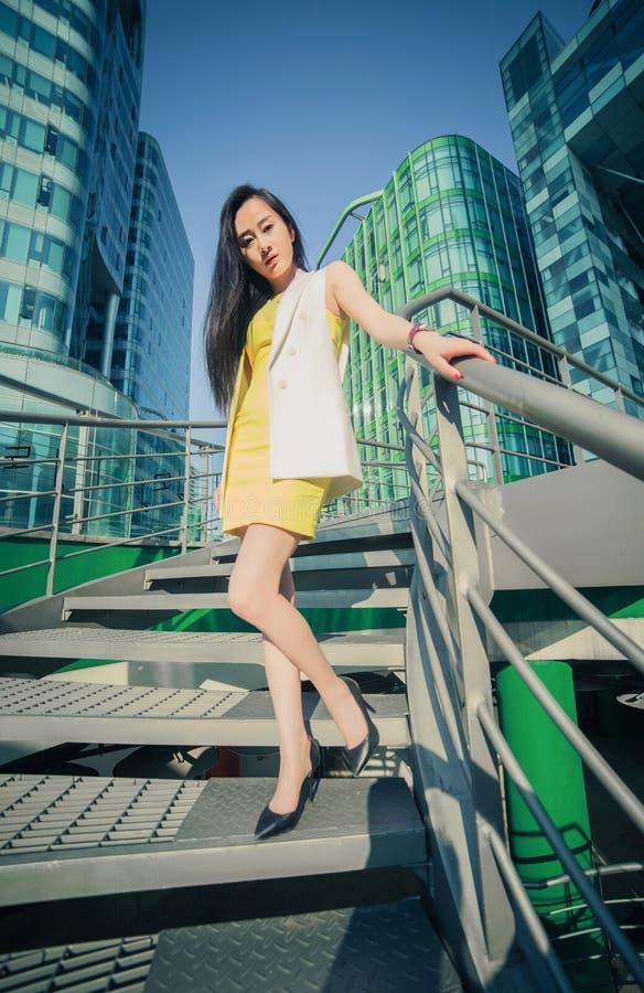 Beau modèle asiatique de fille dans la robe blanche posant près du fond moderne d'escaliers photographie stock