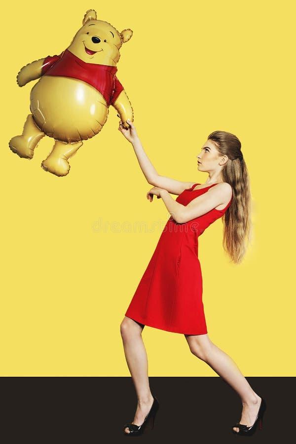 Beau modèle avec le ballon sur le fond jaune images stock