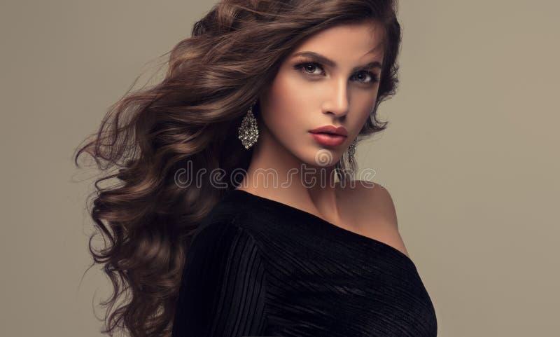 Beau modèle avec longtemps, dense et bouclée la coiffure photo libre de droits
