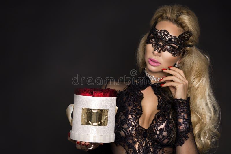 Beau modèle blond dans la robe élégante tenant un cadeau, boîte de fleur avec des roses Cadeau du `s de Valentine image libre de droits