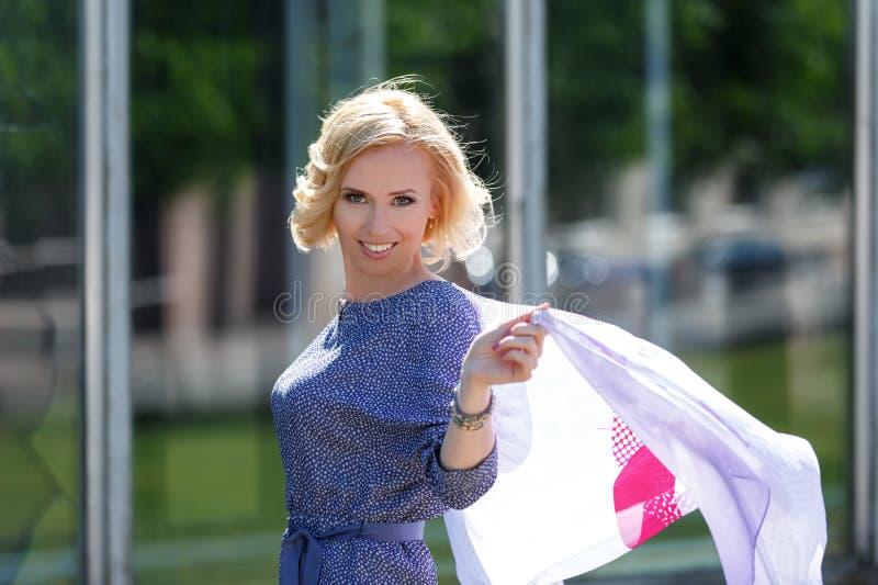 Beau modèle blond de sourire posant avec le foulard de flottement images stock