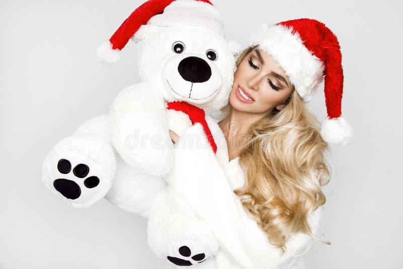 Beau modèle blond sexy et souriant habillé dans un chapeau de Santa Claus, tenant un ours de nounours Fille sensuelle de beauté p images libres de droits