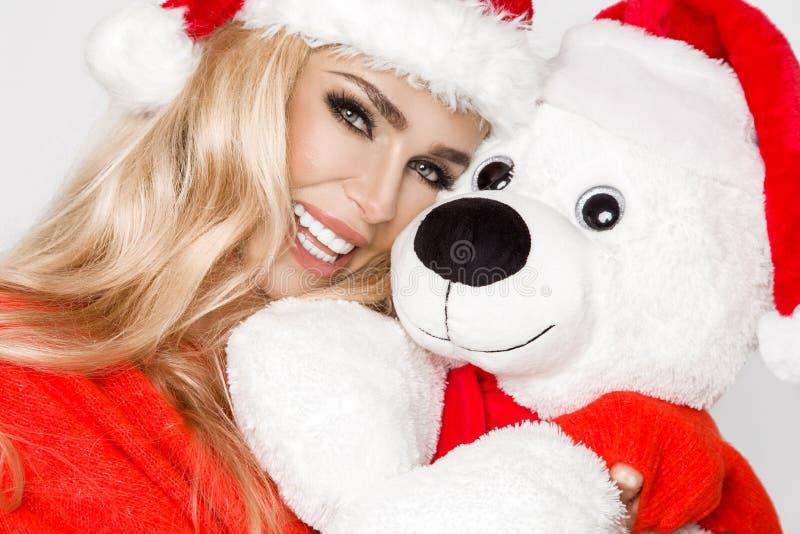 Beau modèle blond sexy et souriant habillé dans un chapeau de Santa Claus, tenant un ours de nounours Fille sensuelle de beauté p photos libres de droits