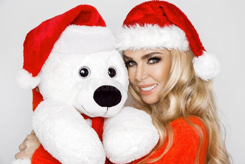 Beau modèle blond sexy et souriant habillé dans un chapeau de Santa Claus, tenant un ours de nounours Fille sensuelle de beauté p photo stock