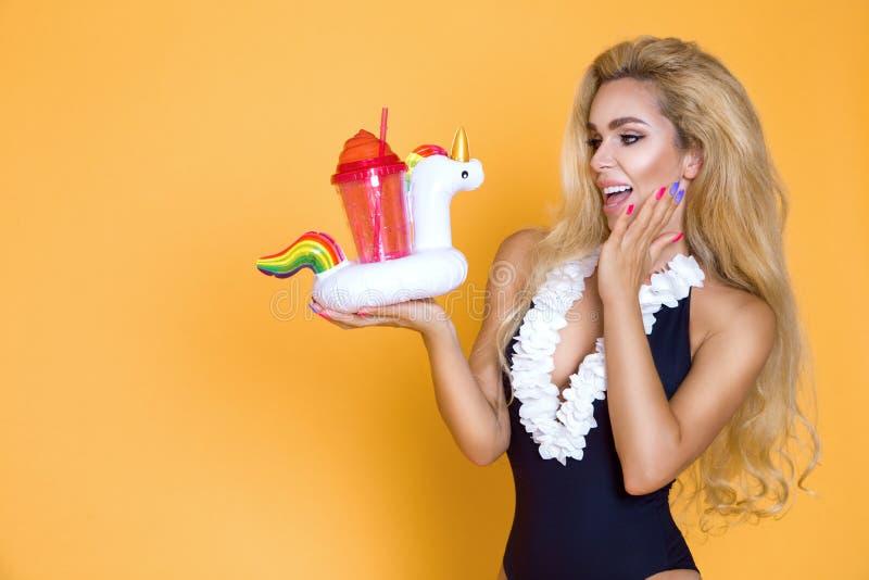 Beau modèle dans un bikini et des lunettes de soleil, tenant une boisson et un flamant rose gonflable photographie stock