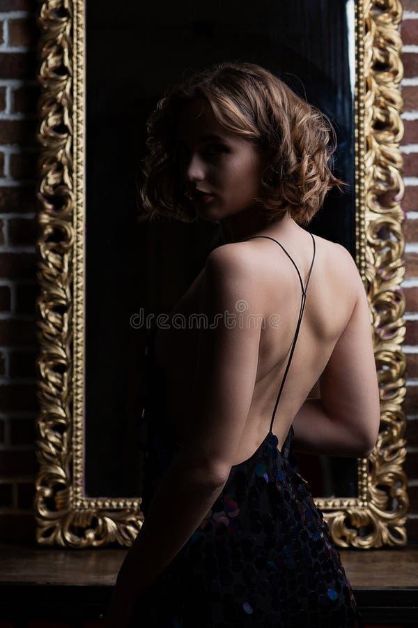 Beau modèle de brune avec le dos nu posant avec la lumière de contraste images libres de droits
