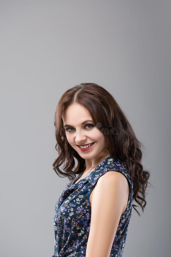 Beau modèle de brune avec le long cheveu brun bouclé Jolies poses de modèle au studio image libre de droits