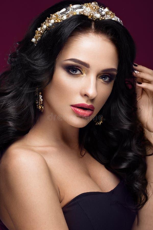 Beau modèle de brune : boucles, maquillage classique, bijoux d'or et lèvres rouges Le visage de beauté photos stock